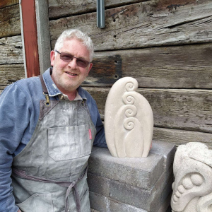 Neil-with-his-unfurling-fern-carved-from-Portland-stone